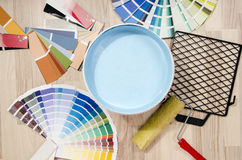 Samples with different shades of blue and can of blue paint with paint roller and accessories. Stock Photography