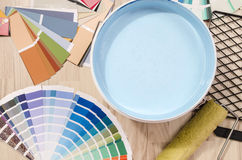 Samples with different shades of blue and can of blue paint with paint roller and accessories. Royalty Free Stock Image