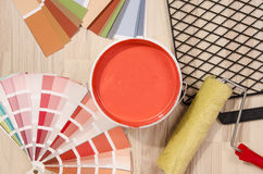 Samples with different shades of red and can of red paint with paint roller and accessories. Stock Photo
