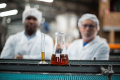Samples of drinks on production line. And two factory engineers standing in background stock photos