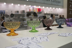 Samples of glass dishes shown on exhibition. Multi colored bowls stands on the table Stock Photo