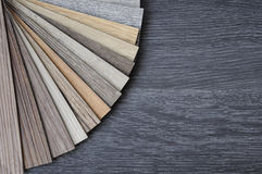 Samples of laminate and vinyl floor tile on black wooden Backgro. Wood texture floor plank on the wooden table for interior choose repair new floor Stock Images