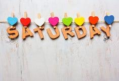 Samstag-Wort von den hölzernen Buchstaben auf einem weißen hölzernen Hintergrund stockfoto