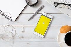 Samsung A5 con l'applicazione di Snapchat che mette su scrittorio Immagini Stock