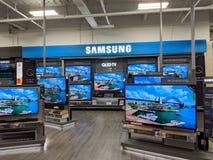 Samsung-Embleem en QLED-TV binnen Best Buy-Opslag stock afbeelding