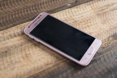 Samsung J3 Pro Smartphone stawia dalej drewnianego stołowego tło Fotografia Royalty Free