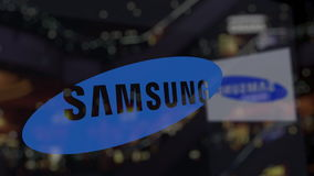 Samsung logo on the glass against blurred business center. Editorial 3D rendering Royalty Free Stock Images