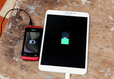 Samsung tablet and nokia mobile phone charging Royalty Free Stock Image