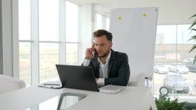 Samtal för affärsledare på mobil till arbetsplatsen i det moderna kontoret, allvarlig affärsman Works på bärbara datorn på intern lager videofilmer