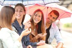 Samtal för fyra vänner som är utomhus- i en regnig dag royaltyfri bild
