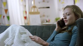Samtal för ung kvinna på mobiltelefonen på en soffa arkivfilmer
