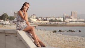 Samtal för ung kvinna på mobiltelefonen på sjösidan arkivfilmer