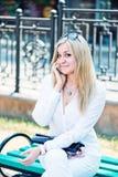 Samtal för ung kvinna vid den utomhus- telefonen Royaltyfria Foton