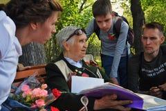 Samtal f?r en krigsveterankvinna till den unga utvecklingen om kriget arkivfoto