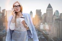 Samtal om avtal Härlig ung kvinna i klassiska kläder som talar på telefonen och rymmer kopp kaffestund arkivbild
