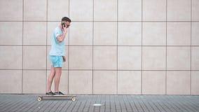 Samtal på telefonen, medan skateboarding arkivfilmer