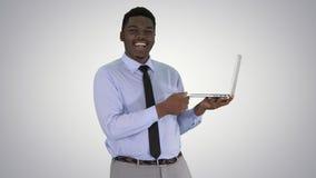 Samtal till den unga afrikanska mannen för kamera med bärbara datorn i hans händer på lutningbakgrund royaltyfri foto
