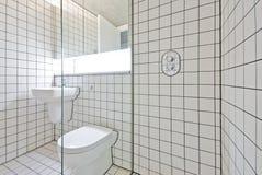 Samtida badrum med retro vita belade med tegel väggar Fotografering för Bildbyråer