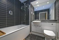Samtida badrum med svarta tegelplattor Fotografering för Bildbyråer