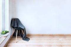 samtida hemmilj? Svart stol som framme täckas med den woolen gråa filten av en tom vit vägg Suckulent växt på arkivbild