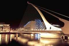 Samuel Beckett Bridge at night. Samuel Beckett Bridge in Dublin, Ireland lit up at night, with a shimmering blue light from the Dublin Convention Centre in the Stock Image
