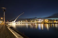 Samuel Beckett bridge at night. Night shot of the Samuel Beckett bridge along the quays in Dublin, Ireland. Dublin City centre is shown in the background Stock Photos