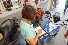 Samui, Таиланд - 5-ое августа 2016; Работник обслуживания рассматривает motobike Стоковое фото RF