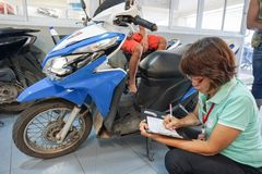 Samui, Таиланд - 5-ое августа 2016; Работник обслуживания рассматривает motobike Стоковые Изображения