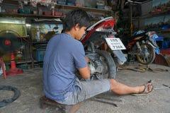 SAMUI ISLAND, THAILAND - 22 MAY 2016: Thai man repairing flat tyre of motorbike. SAMUI ISLAND, THAILAND - 22 MAY 2016: An unidentified Thai man repairing flat Stock Photo