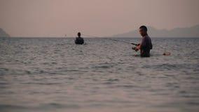 SAMUI, TAILANDIA - 23 DE JUNIO DE 2018: Silueta del pescador en la acción al hacer girar, tiempo de la puesta del sol Empleo asiá almacen de video