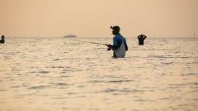 SAMUI, TAILANDIA - 23 DE JUNIO DE 2018: Silueta del pescador en la acción al hacer girar, tiempo de la puesta del sol Empleo asiá metrajes
