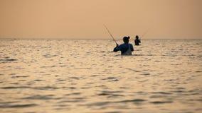 SAMUI, TAILANDIA - 23 DE JUNIO DE 2018: Silueta del pescador en la acción al hacer girar, tiempo de la puesta del sol Empleo asiá almacen de metraje de vídeo