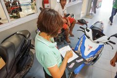 Samui, Thailand - 5 AUGUST 2016; Service worker examine motobike. Samui, Thailand - 5 AUGUST 2016 Asian service worker examine motobike damage Royalty Free Stock Photo
