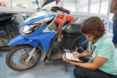 Samui, Thailand - 5 AUGUST 2016; Service worker examine motobike. Samui, Thailand - 5 AUGUST 2016 Asian service worker examine motobike damage Stock Images