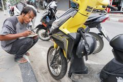 Samui, Thailand - 5 AUGUST 2016; Service worker examine motobike. Samui island, Thailand - 5 AUGUST 2016 Asian service worker examine motobike damage Royalty Free Stock Image