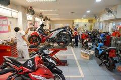 Samui, Thailand - 5 AUGUST 2016; Service workers examine motobike. Samui, Thailand - 5 AUGUST 2016 Asian service worker examine motobike damage at service center Stock Photos