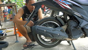 Samui, Thailand - 23 October 2016: Thai man repairing motorbike rear wheel. An unidentified Thai man repairing flat tyre of the motorbike rear wheel stock video