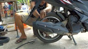 Samui, Thailand - 23 October 2016: Thai man repairing motorbike rear wheel. An unidentified Thai man repairing flat tyre of the motorbike rear wheel stock video footage