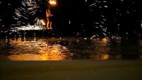 SAMUI, THAILAND - 8TH JANUARY, 2018: Fisherman beach Thai fireshow. Dangerous tricks with flame. Fire performance, sparks fly in all directions, hit the sea stock video footage