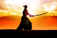 Samurai. Silhouette of a samurai posing during sunset Royalty Free Stock Photography