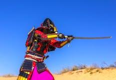 Samurai in armatura antica, con una spada in un attacco Immagine Stock Libera da Diritti