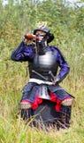 Samurai in armatura che beve dalla boccetta Fotografia Stock Libera da Diritti