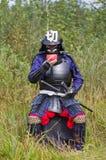 Samurai in armatura che beve dalla ciotola Immagini Stock