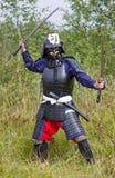 Samurai in armatura con due spade Immagini Stock