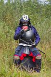 Samurai in armor drinking from bowl Stock Images