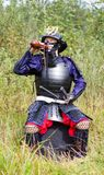 Samurai in armor drinking from flask. Man in Japanese medieval samurai armor (tosei-gusoku) with swords sitting outdoor drinking from brown gourd flask (hyotan Royalty Free Stock Photo