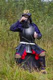 Samurai in armor drinking sake from cup. Man in Japanese medieval samurai armor (tosei-gusoku) with swords sitting outdoor drinking sake from white cup Royalty Free Stock Images