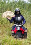 Samurai in armor with fan. Man in Japanese medieval samurai armor (tosei-gusoku) with swords sitting outdoor with traditional Japanese fan Stock Photo