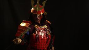 Samurai in armor and mask takes out a katana from the scabbard. Samurai in red armor, helmet and a protective mask slowly pulls the katana out of the scabbard stock footage