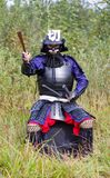 Samurai in armor showing direction by folded fan. Man in Japanese medieval samurai armor (tosei-gusoku) with swords sitting outdoor pointing direction by folded Royalty Free Stock Images